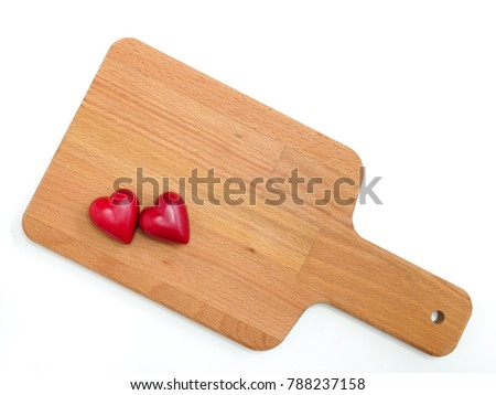 two heart-shaped chocolate candies on a cutting board, top view, closeup, isolated on white background
