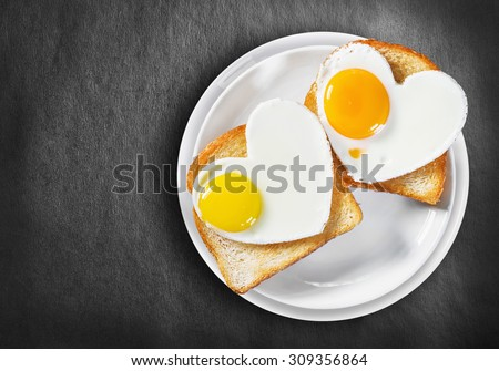Two heart-shaped fried eggs and fried toast on a black background - stock photo
