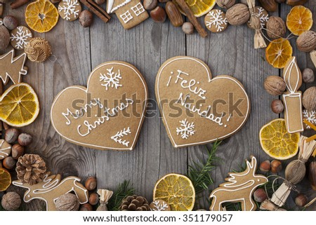 Two heart shaped Ginger breads with white icing, on wooden background, with Merry Christmas written in English and Spanish