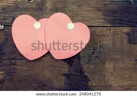 Two heart-shaped sticker on an old wooden board - stock photo