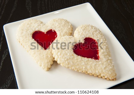 Two heart shaped sugar cookies with strawberry filling on a white plate