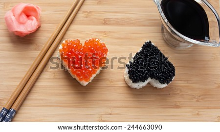 Two heart shaped sushi with salmon roe and beluga caviar on wooden desk. ginger, chopsticks and soy sauce. - stock photo