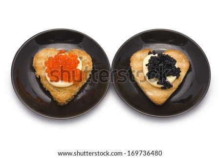 Two Heart-Shaped Toasts with Red and Black Caviar on White Sauce isolated on white - stock photo