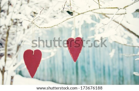 Two heart shaped valentine's / christmas red decorations hanging on the tree bench with blue fence and snow on the background - stock photo