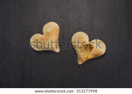Two heart shaped valentines crackers isolated on black stone background with copy space. One perfect and one broken cracker. - stock photo