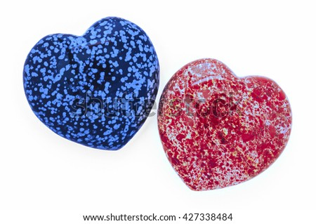 Two heart stones in blue and red, inclined to each other - stock photo
