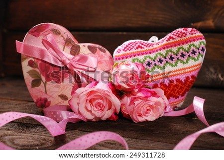 two hearts and pink roses lying on old wooden background  - stock photo