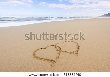 two hearts drawn into the sand at remote beach of Fuerteventura