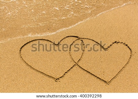 Two hearts drawn on the sand of a sea beach. - stock photo