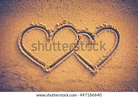 Two hearts handwritten on seashore sand. Valentine's day on the beach. Vignette and vintage picture style. Warm tone. - stock photo