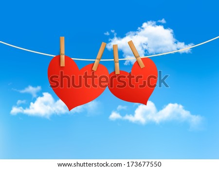 Two hearts hanging on a rope in front of a sky. Valentine's day background. Raster version. - stock photo