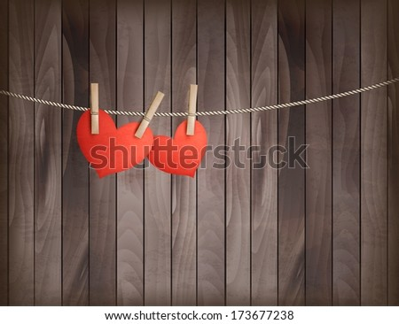 Two hearts hanging on a rope in front of wooden background. Raster version.  - stock photo