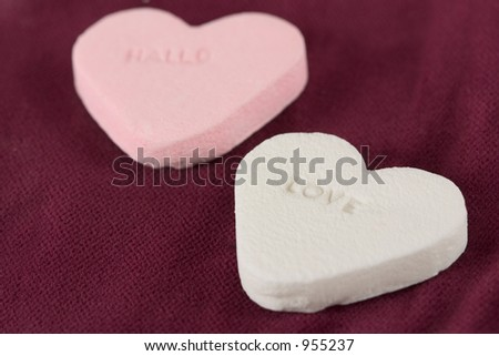 Two hearts of candy on red background