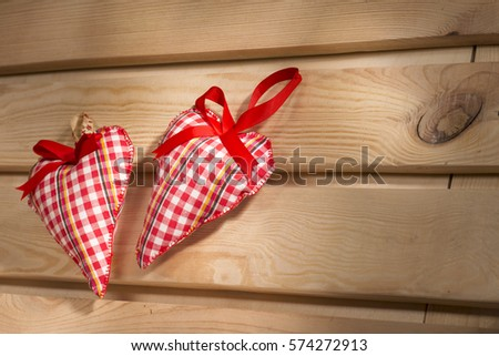 two hearts sewn from red plaid fabric on the board, a symbol of love