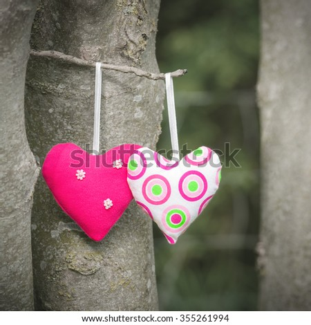 Two hearts together; One for you - one for me; Two handmade textile hearts hanging on a tree - stock photo