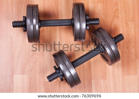 Two heavy dumbbells on a floor