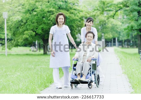 Two helpers walking whilst pushing a wheelchair