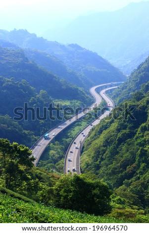 Two highways winding through a mountain range during the day.