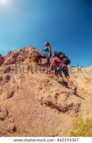 Two hikers climbing up the rocky hill in the desert at sunny day