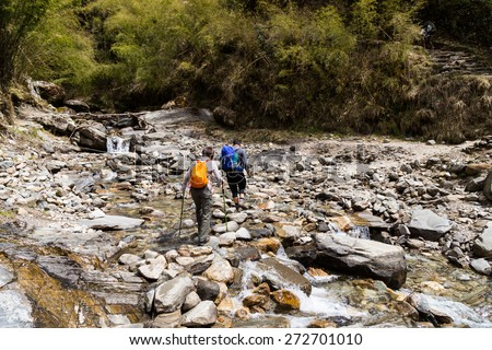 Two hikers crossing a scenic shallow rocky river - stock photo