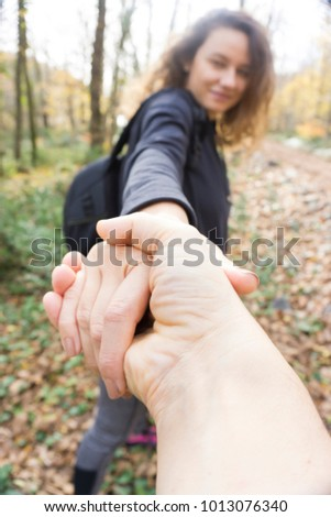 Two hikers in nature. Close Up of man and woman holding hands while walking pathway