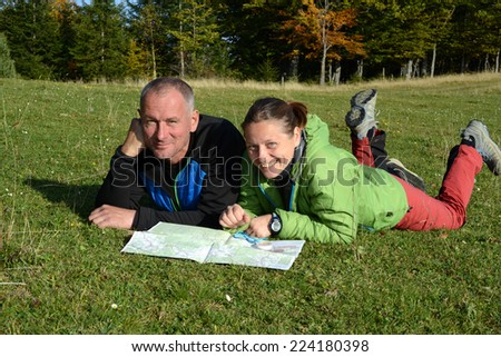 Two hikers looking at map - stock photo