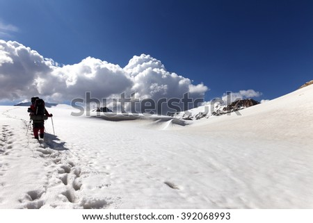 Two hikers on snowy plateau. Turkey, Central Taurus Mountains, Aladaglar (Anti-Taurus), plateau Edigel (Yedi Goller). Wide angle view.
