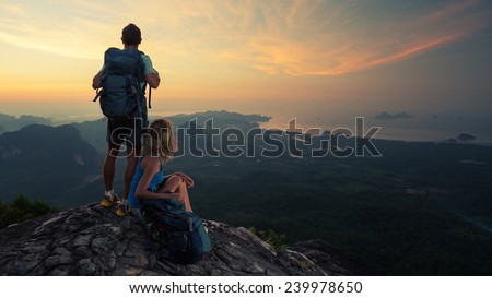 Two hikers on top of the mountain enjoying sunrise over the tropical valley - stock photo