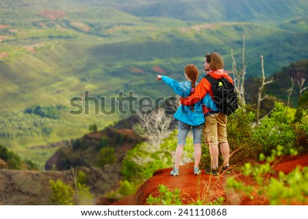 Two hikers relaxing enjoying the amazing view from the mountain top - stock photo