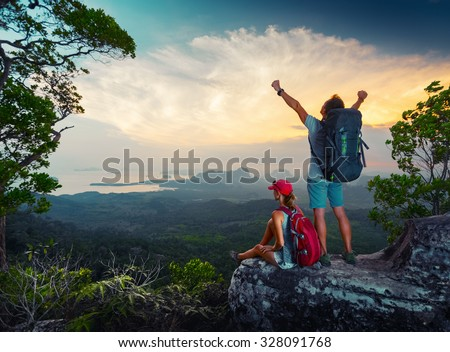 Two hikers relaxing on top of the mountain and enjoying sunset valley view