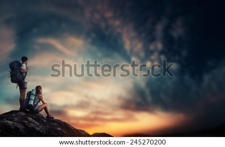 Two hikers relaxing on top of the rock and enjoying sunset - stock photo