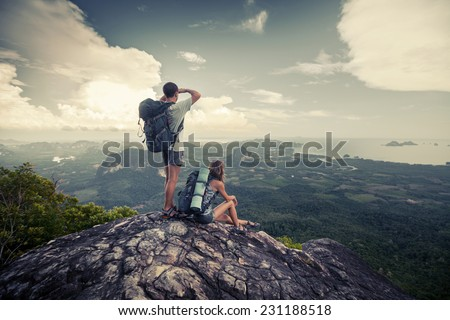 Two hikers standing on top of the mountain - stock photo