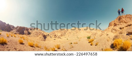 Two hikers standing on top of the mountain in the desert at sunny day - stock photo