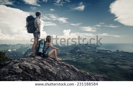 Two hikers standing on top of the mountain with valley on the background - stock photo