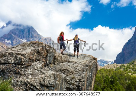 Two hikers staying on rock. Young female travelers on top of high stone wall observing mountain landscape sunny day holding walking poles with backpacks on