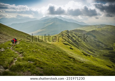 Two hikers / tourists walking on a mountain path during a fine summer day. - stock photo