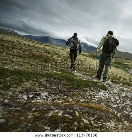 Two hikers walking - stock photo