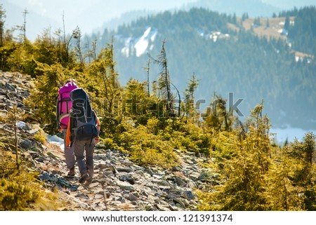 Two hikers walking in autumn mountains. Caucasian model outdoors in nature