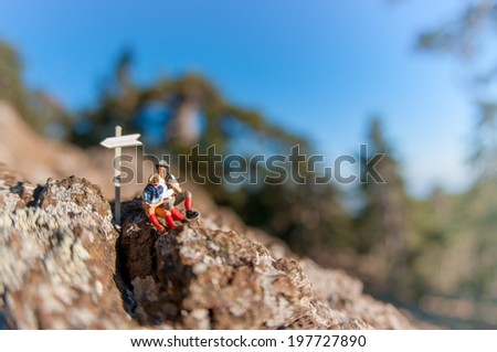 Two hikers with backpack relaxing on top of a mountain. Macro photography - stock photo