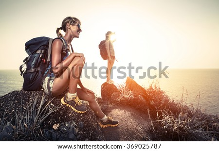 Two hikers with backpacks relaxing on the rock and enjoying tropical sunset