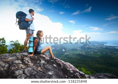 Two hikers with backpacks standing on top of a mountain and looking to a valley - stock photo