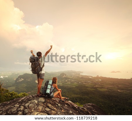 Two hikers with backpacks standing on top of a mountain with great valley view - stock photo