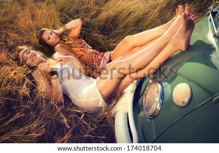 two hippie girls in the grass - stock photo