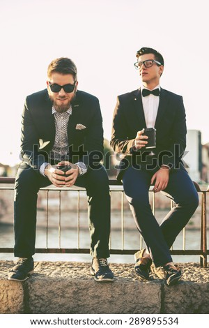 Two hipster friends having fun outside, drinking coffee and chatting, shallow depth of field - stock photo