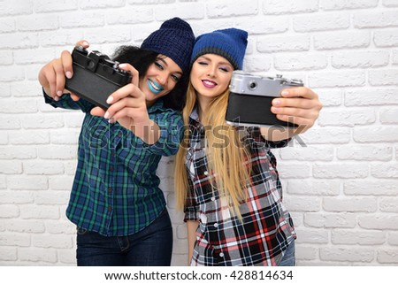 Two hipster girls taking photo with retro cameras over white wall. - stock photo