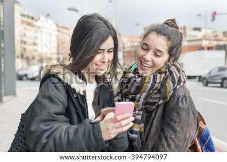 Two hipster joy woman friends using smart phone.