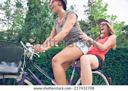 Two Hipster Young Women Having Fun On Bike In Park - stock photo