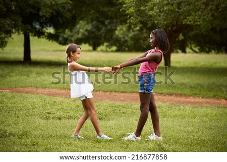 Two hispanic and african little girls playing ring around the rosie in public park and holding hands