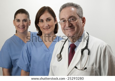 Two hispanic nurses on white background with mature male doctor - stock photo
