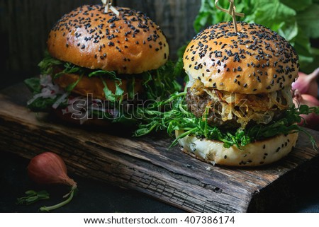 Two Homemade burgers with beef, fried onion and pea sprouts, served on wooden chopping board over wooden background. Dark rustic style. Natural day light. - stock photo